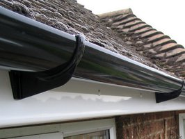 Perfectly aligned high gloss black guttering installation.
